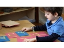 pedagogia montessori. Copil lucrând cu literele din glașpapir